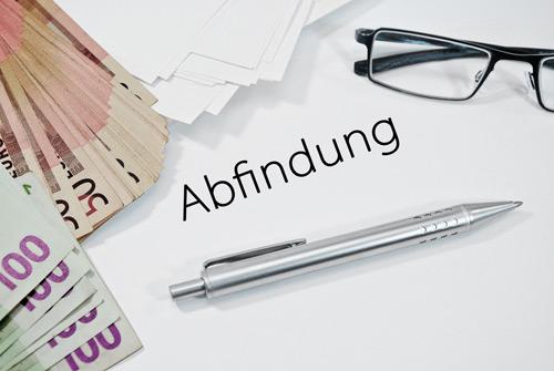 Abfindung Geld auf Tisch - im Aufhebungsvertrag Arbeitsrecht wird oft Abfindung vereinbart.